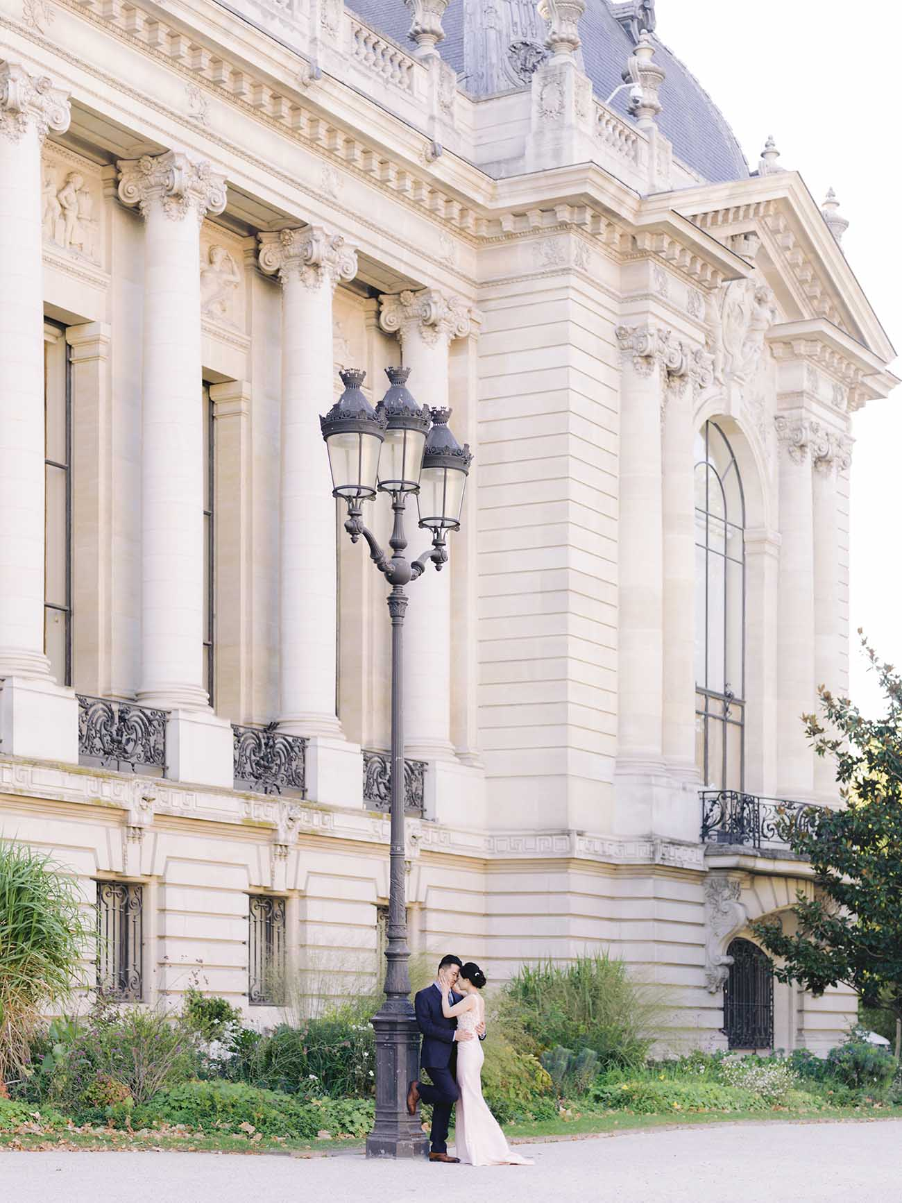A couple kissing in front of the Petit Palais in Paris