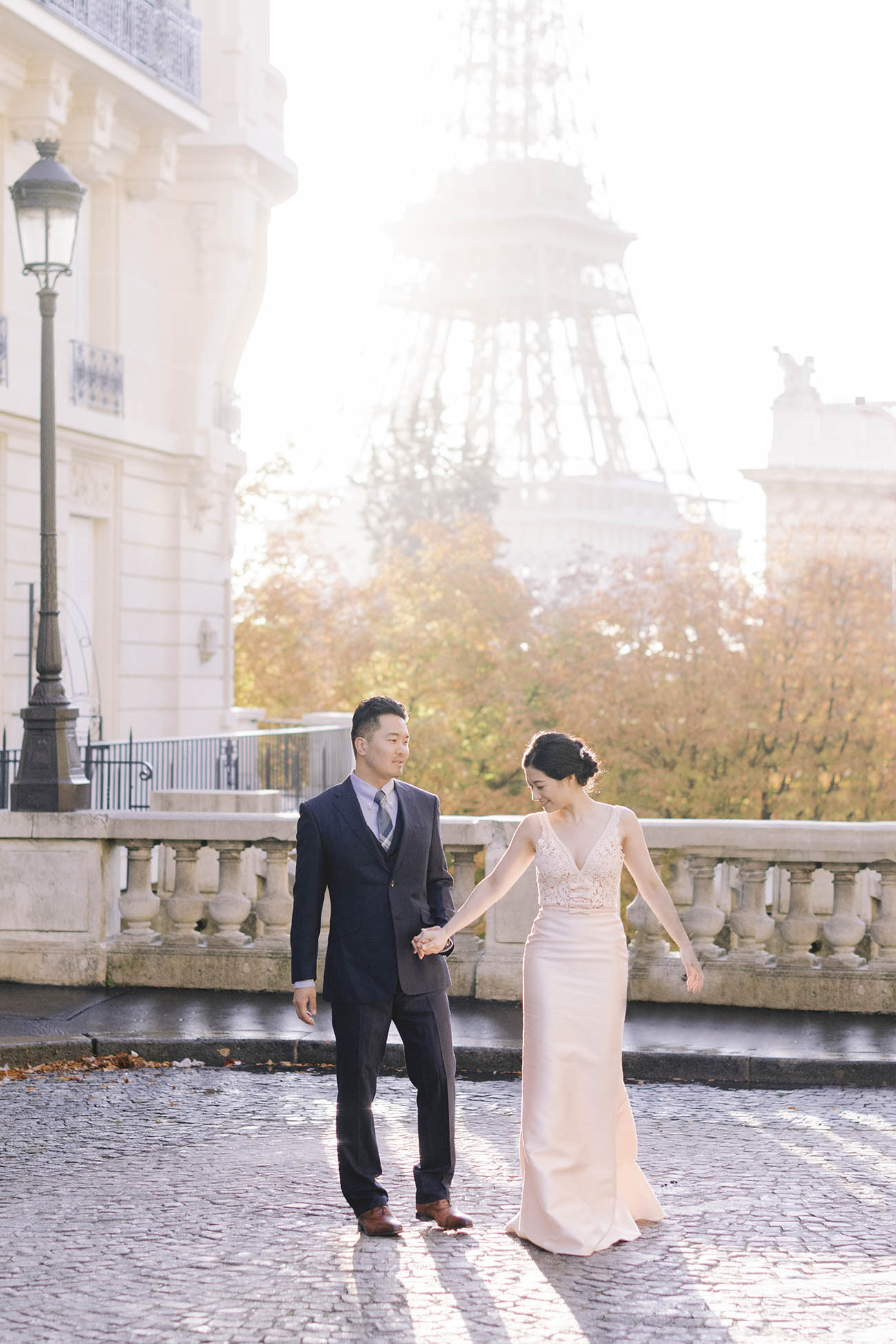 of the bride and groom walk on the street. Behind them the eiffel tower lit by morning light