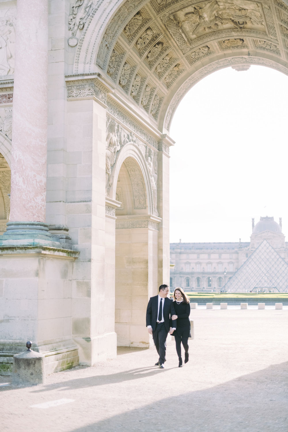 lovers are walking at the louvre museum in paris.