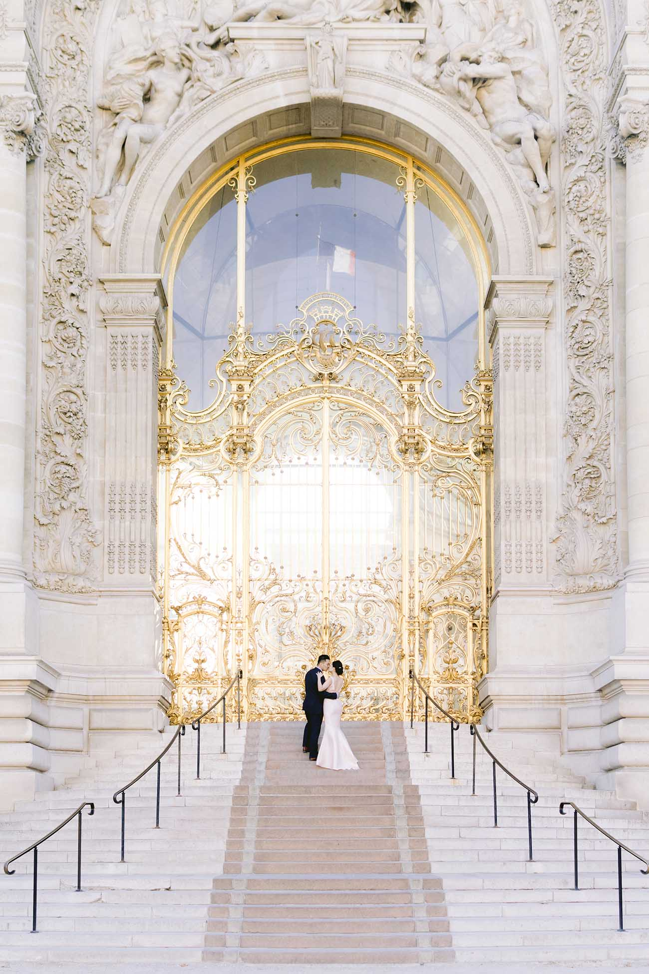 A couple embraces in front of the magnificent golden door of the Petit Palais in Paris